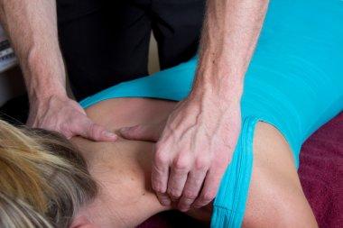Chiropractor massage the patient on her shoulders
