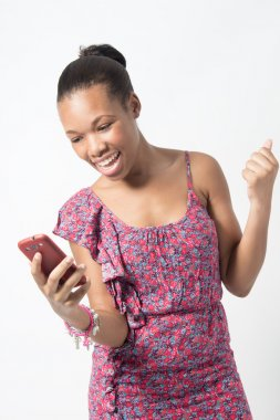 Young African woman excited over text message