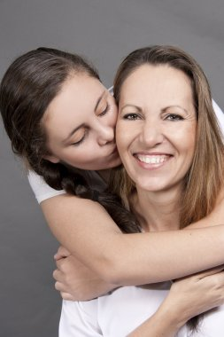 Playful Teenage Daughter Kissing Mom on cheek