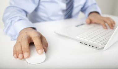 Image of male hand touching computer mouse and keyboard