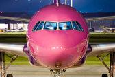 Fotografia vicino del naso di un airbus viola parcheggiata di notte