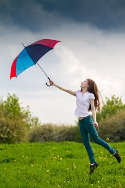 Beatiful girl jumping with coloured umbrella