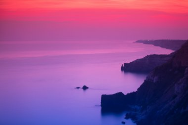 Purple and pink sunset over ocean shore