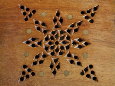 piece of wood with inlays and perforated