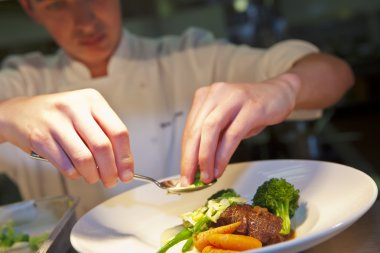 Closeup of chef adding finishing touch on his dish