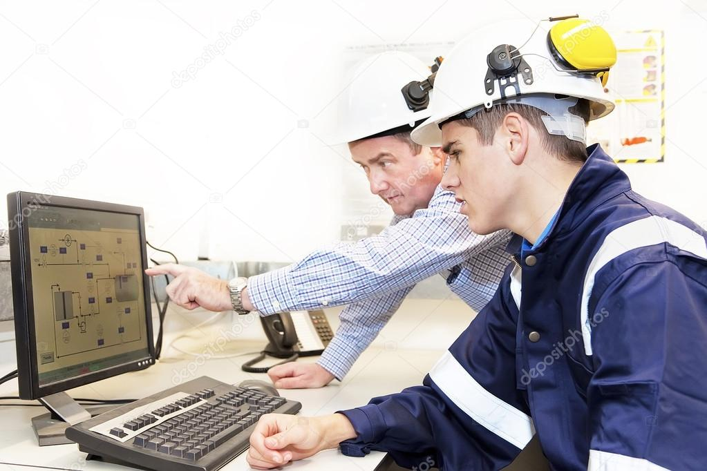 Senior and junior engineers discussing work together in office