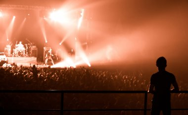 Silhouette of man, watching a bang on stage