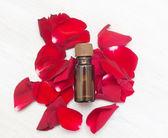 Fényképek üveg aromaterápiás olajat és a fényes vörös rózsa, a beauty spa