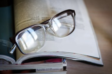 glasses for reading on a stack of magazines, in soft focus