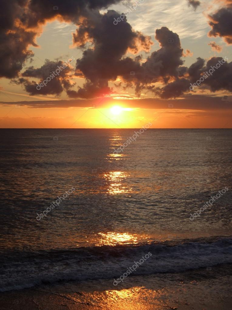Amber sunset with the solar track on sea rounded waves