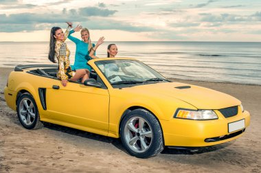Three girls with sport car on a beach