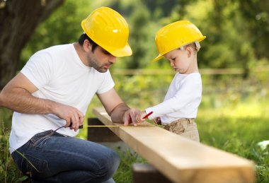 Little son helping his father with building work stock vector