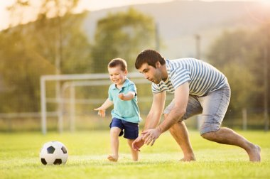 Young father with his little son playing football on football pitch stock vector