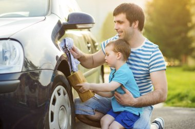 Father with son washing car