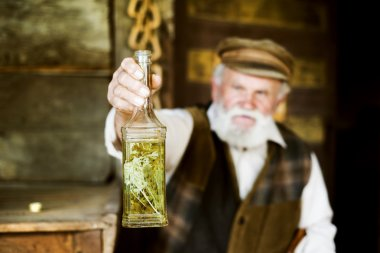 Farmer with bottle of herbal spirit