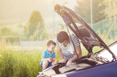 Father with son repairing car