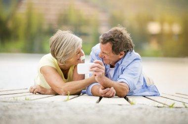 Senior couple lying on pier