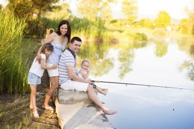 Family with kids fishing in pond