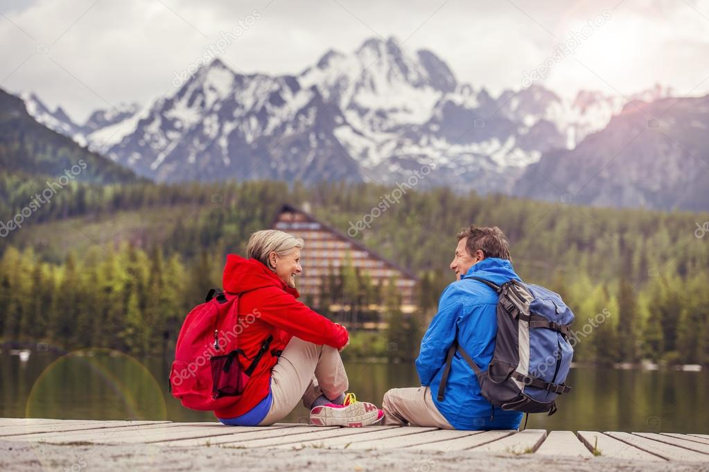 Senior hikers couple resting on pier