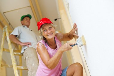 Senior couple painting wall with brush