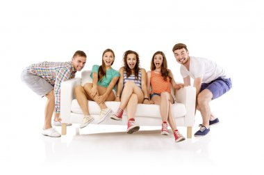 Men lifting sofa with women sitting on it,