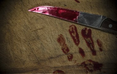 Grunge wooden background with a bloody hand print on the cutting board
