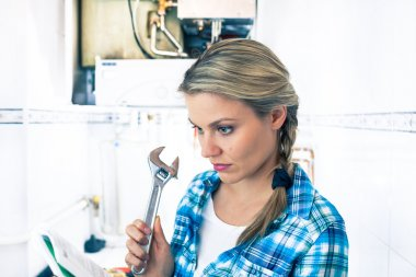 Beautiful Girl Is Learning How To Repar a Boiler Using a Pipe Wrench