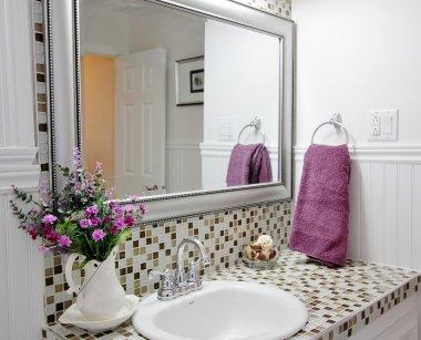 Elegant country bathroom with purple flowers in vase and purple towel