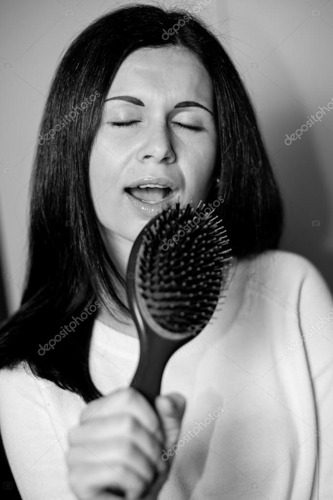 Joven morena alboroto-headed pretendiendo cantar con su cepillo de pelo  como micrófono — Foto de dachazworks1 eb91ec15670a
