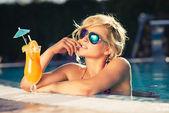 Fotografie Mädchen mit frisch gepresstem Orangensaft im Luxus-pool