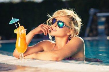 girl with fresh orange juice in luxury pool