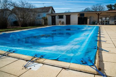 Pool protected by a pool cover during winter months