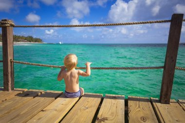 A small child sits on the edge of the pier