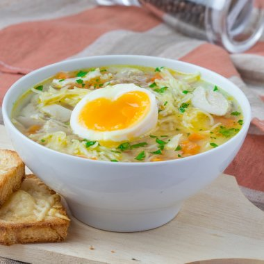 Chicken soup with noodles, carrots and cheese croutons