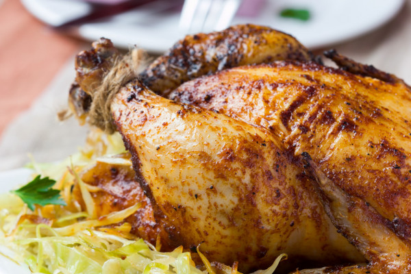 Roasted whole chicken with golden crust and garnish of stewed ca