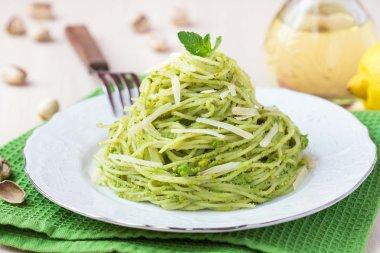 Italian green pasta spaghetti with pesto green peas, mint, pista