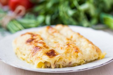 Italian pasta Cannelloni stuffed with meat, white Bechamel sauce
