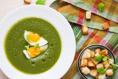Green spring, summer healthy cream soup with herbs, egg, crouton