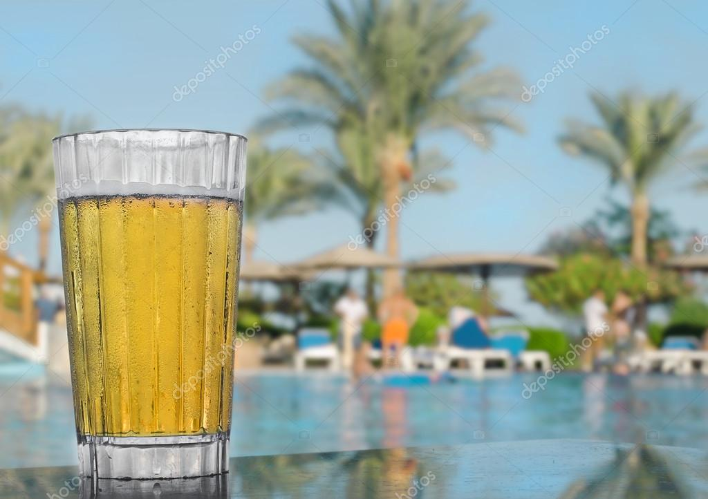Glass of cold beer on the table , against the backdrop of palm trees. Egypt resort.