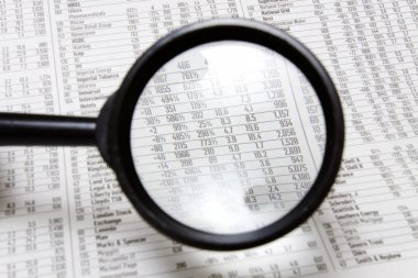 Magnifying glass over stocks and shares