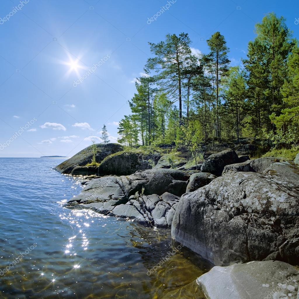Sun and stony shore of Ladoga lake