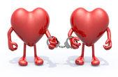 Fotografie zwei Herzen mit Armen und Beinen, die durch Handschellen an Händen verbunden sind