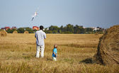 Father and son controls RC plane in the sky