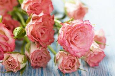 Pink roses bouquet on wooden table