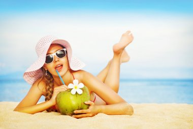 Young woman in pink swimsuit with coconut cocktail on the beach, bali