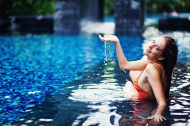 Young woman in the pool in luxury resort, Bali, Indonesia