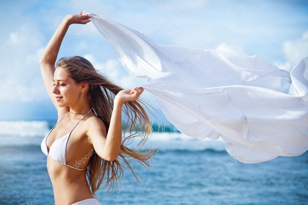 Young beautiful woman holding white scarf near ocean, Indonesia, Bali