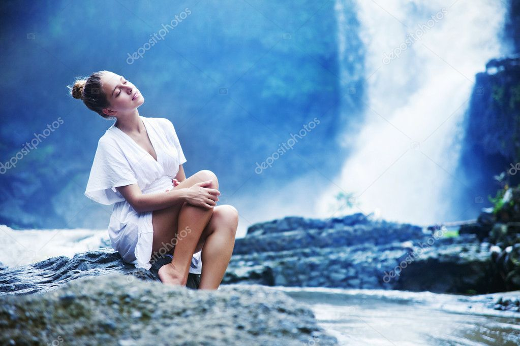 Young woman near waterfall, bali, indonesia