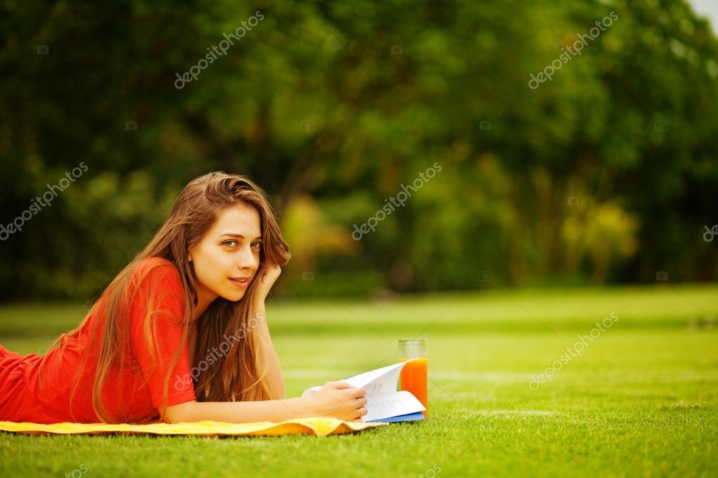 Young woman on the grass with book and orange juice