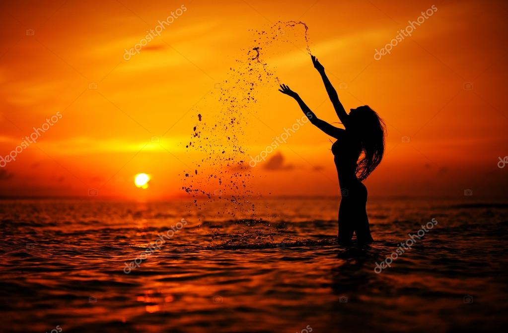 Long hair woman silhouette in the sea splashing water